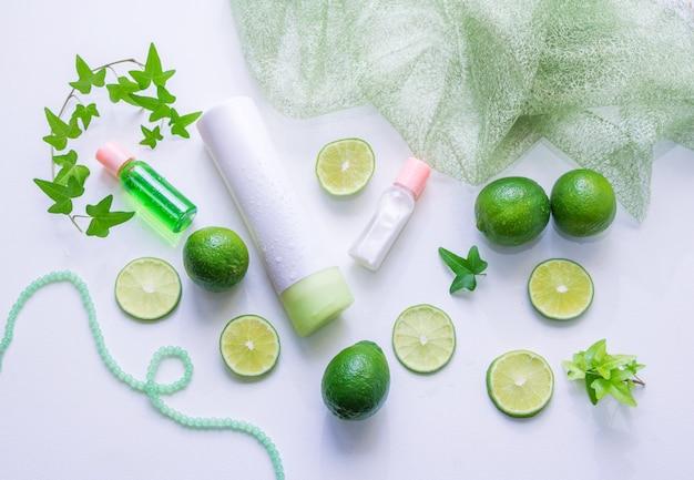 Лосьон для лица и тоник в бутылках, ломтики лайма, зеленые листья - использование цитрусовой эссенции для концепции косметических продуктов Premium Фотографии