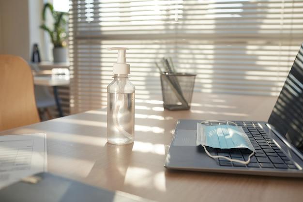 Маска для лица и дезинфицирующее средство для рук на пустом рабочем столе в офисе после пандемии, освещенном солнечным светом Premium Фотографии