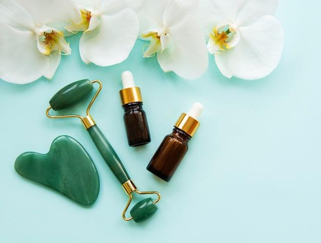 パステルグリーンの表面に翡翠ローラーと化粧品を使ったフェイスマッサージ Premium写真