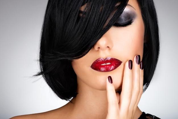 아름다운 어두운 손톱과 섹시한 붉은 입술을 가진 여자의 얼굴. 검은 머리를 가진 패션 모델 무료 사진
