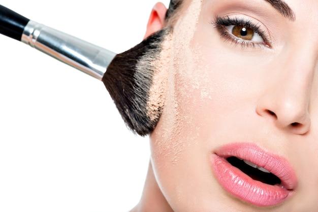 頬の皮膚にパウダーを塗った女性の顔 無料写真