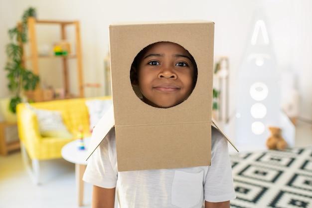 彼の頭の段ボール箱の穴からアフリカ民族のかわいい男の子の顔 Premium写真
