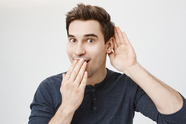 Лицо возбужденного парня узнало интересные сплетни, подслушивая Бесплатные Фотографии