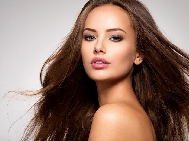 긴 갈색 머리 포즈와 아름 다운 여자의 얼굴 무료 사진