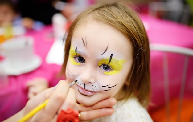 Face painting for cute little girl during kids birthday party Premium Photo