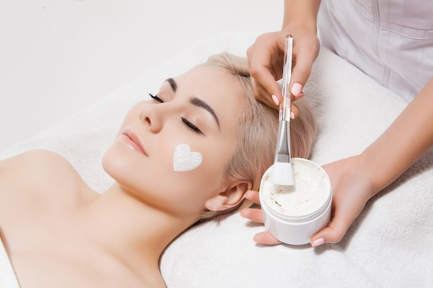 Face peeling mask, spa beauty treatment, skincare. woman getting facial care by beautician at spa salon. model lying on couch with closed eyes. cosmetological clinic. healthcare, clinic, cosmetology Premium Photo