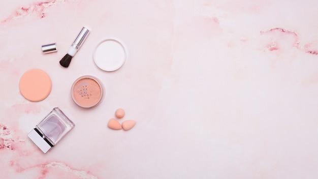 Face powder; makeup brush; powder puff; bottle and blender on pink backdrop Free Photo