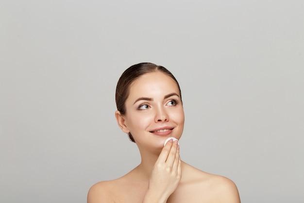 얼굴 피부 관리. 목화 패드와 함께 메이크업을 제거하는 아름 다운 여자 프리미엄 사진
