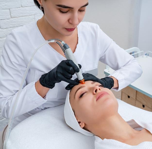 Уход за кожей лица. макрофотография чистки лица женщины в косметологической клинике, пылесос Premium Фотографии