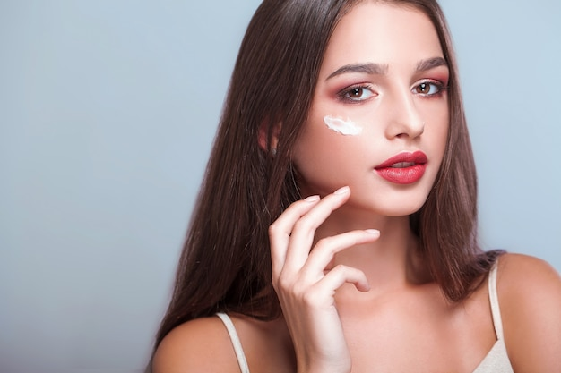 Face treatment. woman with healthy face applying cosmetic cream under the eyes Premium Photo