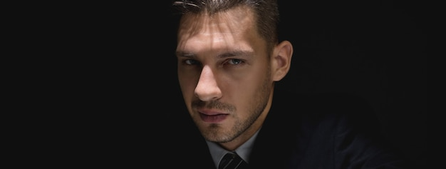 Face of tricky sly man staring at the camera in dark shadow Premium Photo