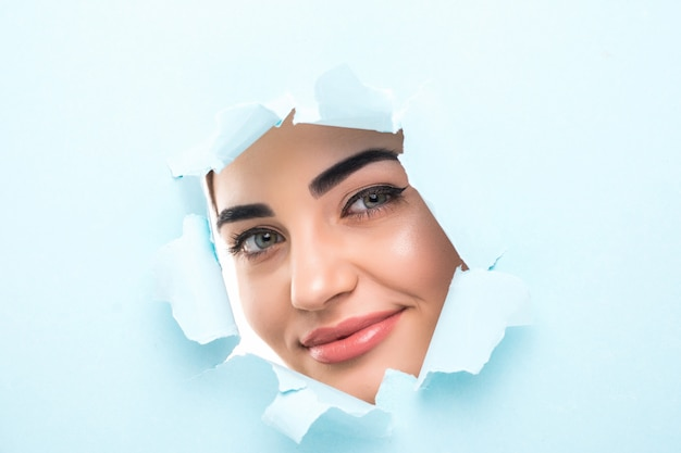The face of a young beautiful woman with a bright make-up and puffy blue lips peers into a hole in blue paper. Free Photo