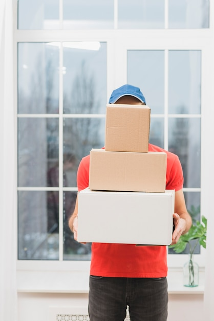 Faceless courier with stack of parcels Free Photo