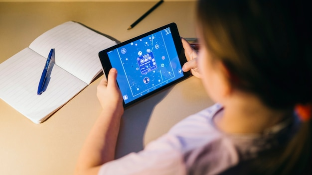 Faceless girl playing tablet game while studying Premium Photo
