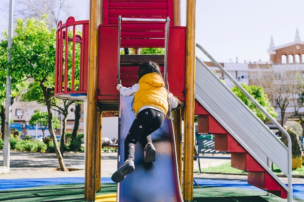 Faceless girl trying to climb slide Free Photo
