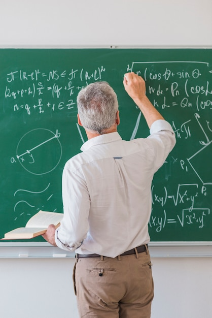 Faceless lecturer chalking formula on blackboard Premium Photo