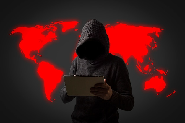 Faceless man in a hoodie with a hood holds a tablet in his hands on a dark wall. concept of hacking user data. hacked lock, credit card, cloud, email, passwords, personal files Premium Photo