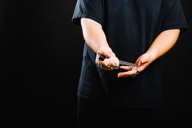 Faceless man posing with dagger Free Photo