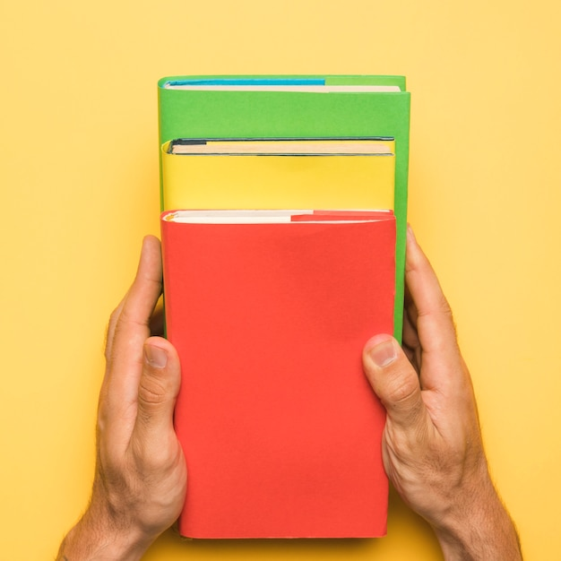 Faceless person holding colorful  books on yellow background Free Photo