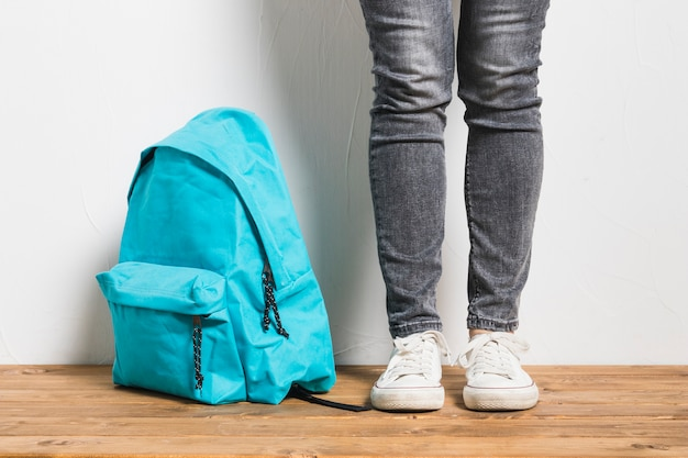 Faceless person standing beside of schoolbag on wooden table Free Photo