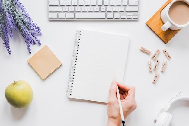 コーヒーカップとキーボードで白いテーブルにノートに書く顔のない人 Premium写真