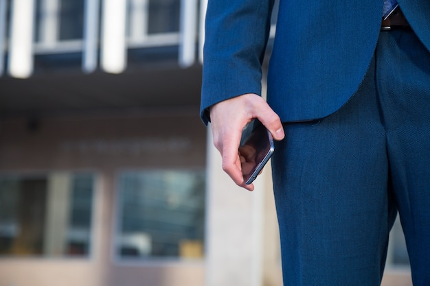 Faceless shot of man in trendy suit holding phone while standing with hand in pocket on street. Premium Photo