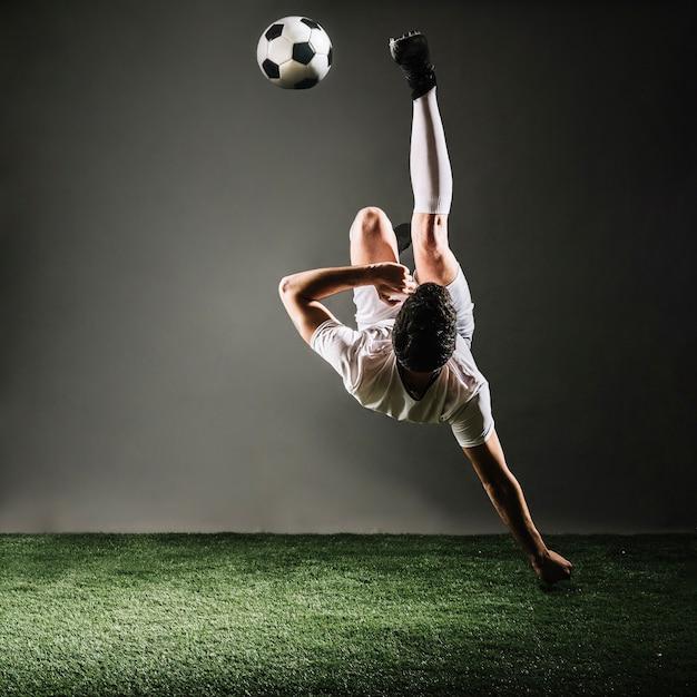 Faceless sportsman falling and kicking ball Free Photo