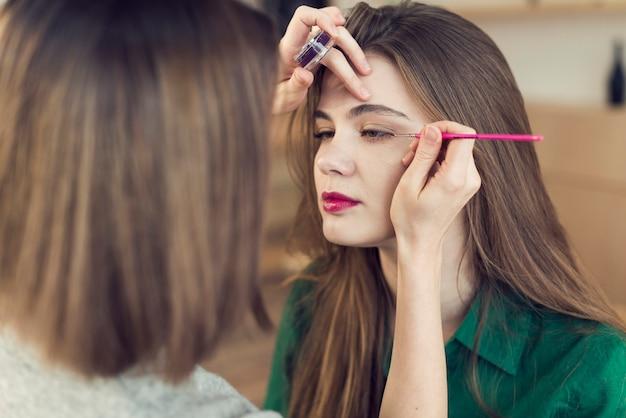 Faceless stylist applying eyeliner on model Free Photo
