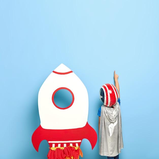 Безликий до неузнаваемости ребенок стоит спиной к камере, в шлеме и серой накидке Бесплатные Фотографии