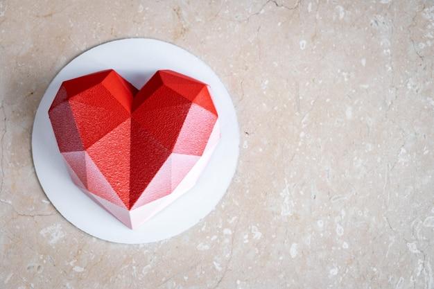 부드러운 핑크색 대리석 테이블에 벨루어 코팅 처리 된 레드 하트 무스 케이크. 프리미엄 사진