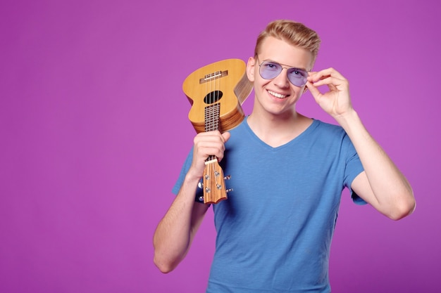 Fachion beauty funny man with ukulele in hands on purple background copyspace Premium Photo