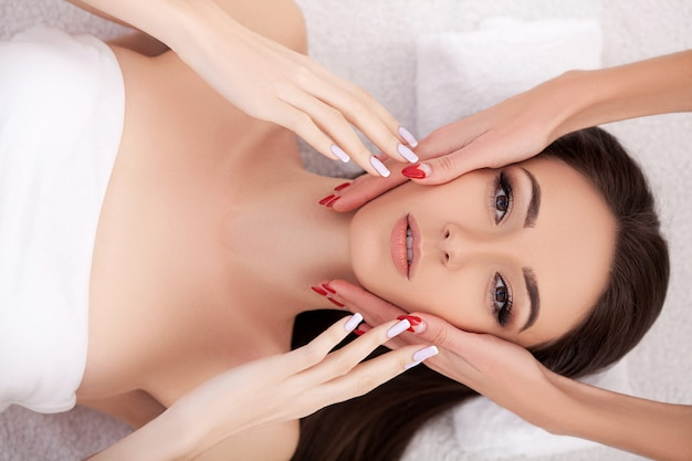 Facial beauty treatment. closeup of beautiful woman getting beauty treatment, hand massage at day spa salon. massauer massaging female face with aromatherapy oil. skin and body care. Premium Photo