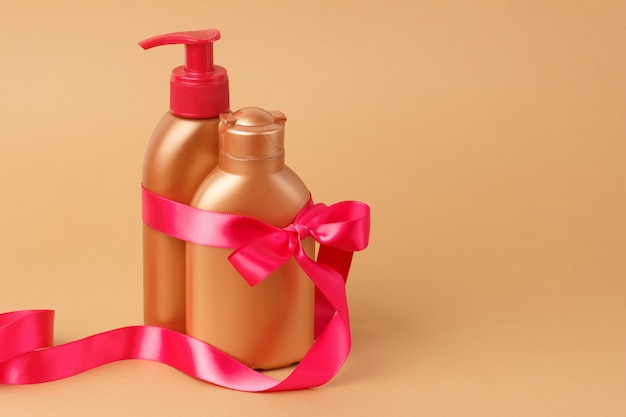 Facial, body skin care on beach, sea on summer vacation. set for safe tan with pink satin ribbon on bronze background. copyspace. Premium Photo