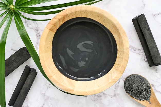 Facial mask and scrub by activated charcoal powder on marble table Premium Photo
