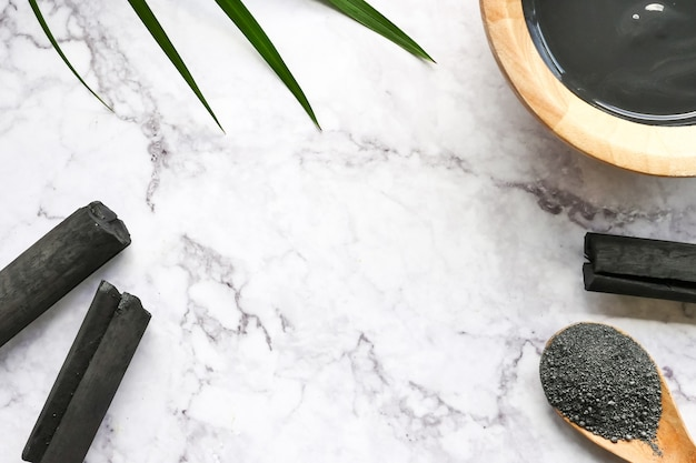 Facial mask and scrub by activated charcoal powder on marble table. Premium Photo