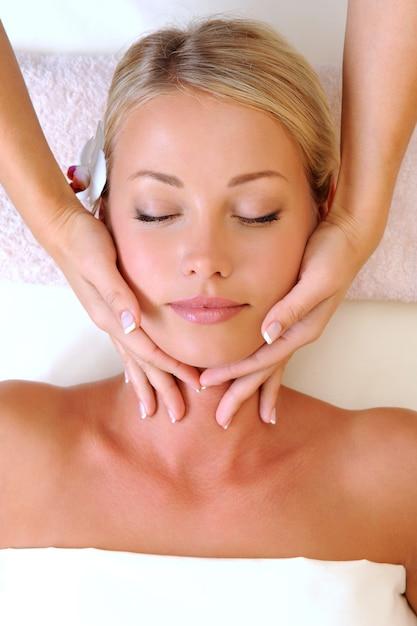 Massaggio facciale per bella giovane donna nel salone di bellezza Foto Gratuite