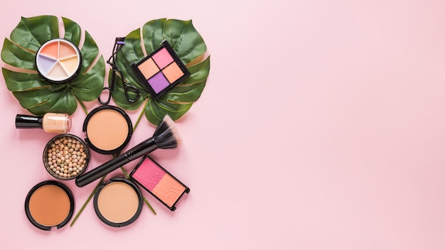 Facial powders with eye shadows and leaves on pink table Free Photo