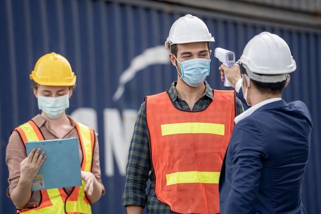 공장 남자 사용 장비는 작업자 온도를 측정합니다. 프리미엄 사진