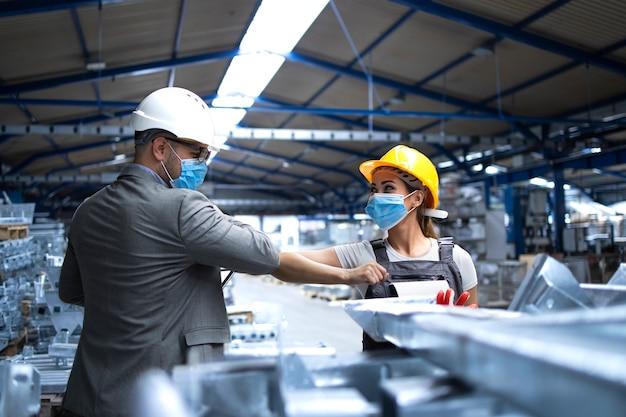 Директор фабрики посещает производственную линию и приветствует работника локтями из-за вируса короны Бесплатные Фотографии