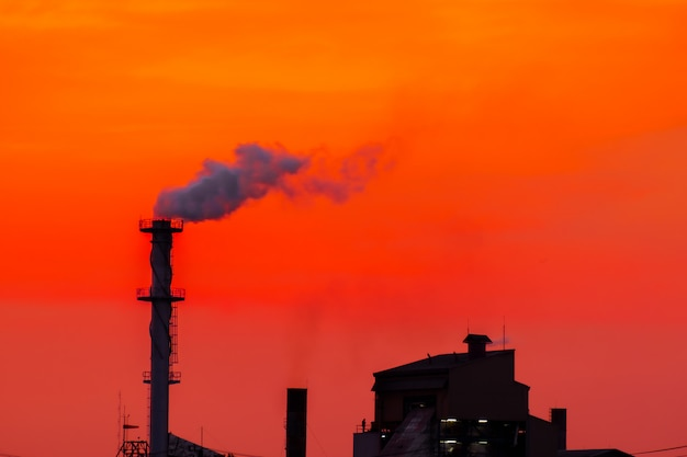 The factory released smoke chimney in sunset global warming Premium Photo