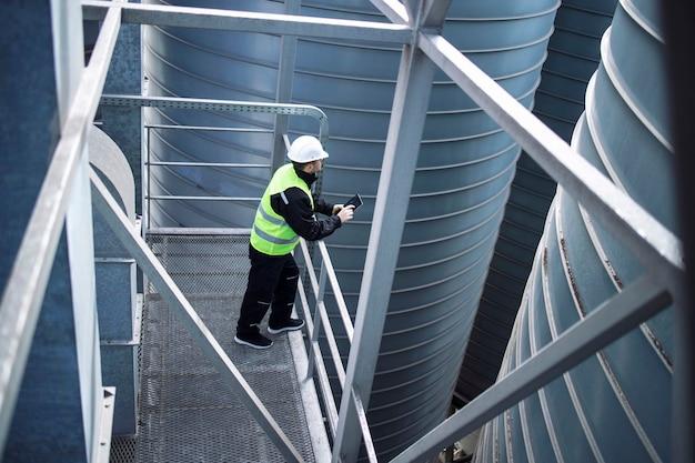 Рабочий завод силосов стоит на металлической платформе между промышленными резервуарами для хранения и смотрит на табличку о производстве продуктов питания Бесплатные Фотографии