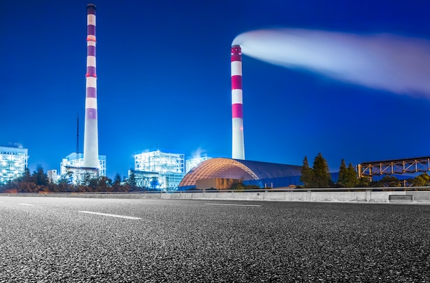 Factory with smoke stack against sky at night Free Photo