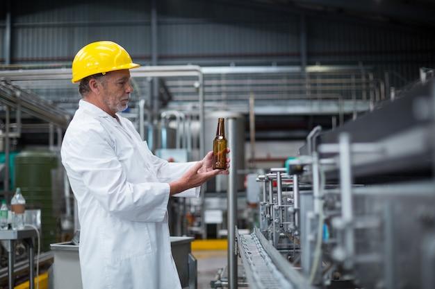 工場でボトルを調べる工場労働者 Premium写真
