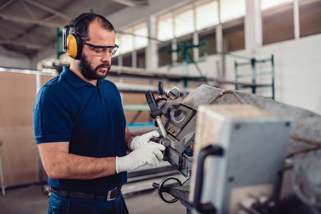 Factory worker operating band saw cutting machine Premium Photo