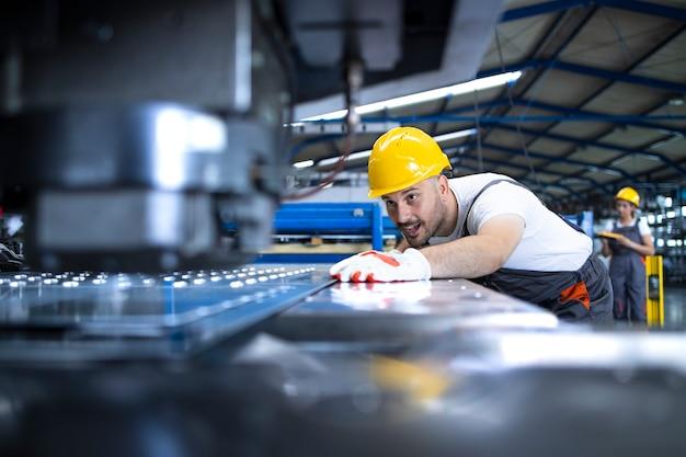 Operaio di fabbrica in uniforme protettiva e elmetto protettivo che opera macchina industriale alla linea di produzione Foto Gratuite