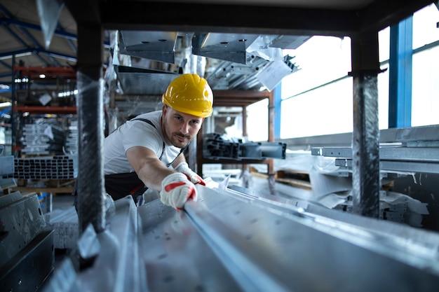 Operaio di fabbrica che lavora nel magazzino di movimentazione di materiale metallico per la produzione Foto Gratuite