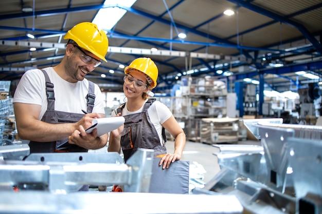 대형 산업 홀에서 제품의 품질을 확인하는 공장 근로자 무료 사진