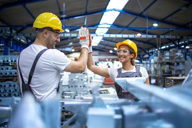 I lavoratori della fabbrica si salutano per il successo del lavoro di squadra Foto Gratuite