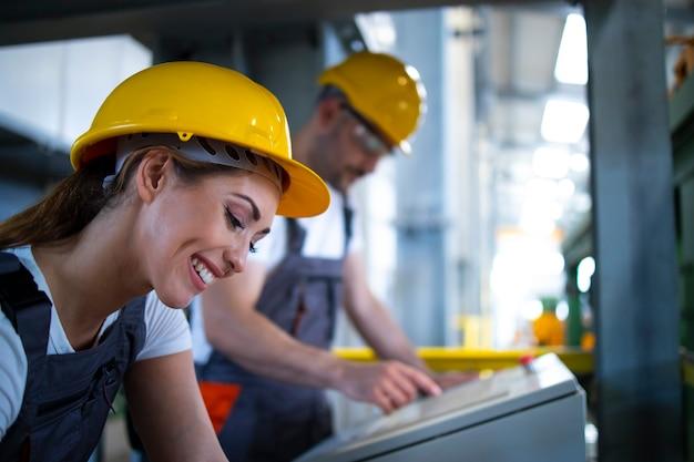 Заводские рабочие в диспетчерской, управляющие промышленными машинами удаленно на производственной линии Бесплатные Фотографии