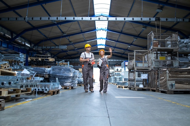 Factory workers walking through large production hall Free Photo